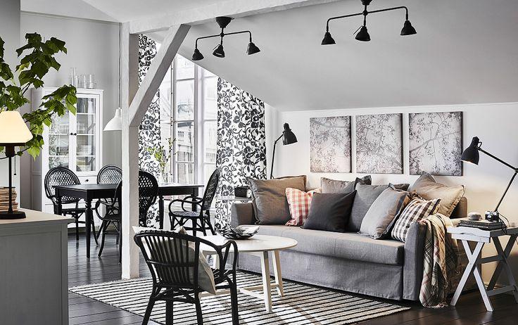 Séjour clair meublé avec un convertible trois places gris clair, une table basse ronde blanche et un fauteuil en rotin noir.