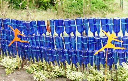 bottle art for the yard | More blue bottles: Here, they are mounted upside down on rebar posts ...
