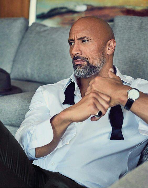 Dwayne Johnson portant une barbe noire et gris et une simple chemise blanche #style #menstyle #bald #guy #beard #look #dwaynejohnson #therock #movie #actor #look #mode #chauve