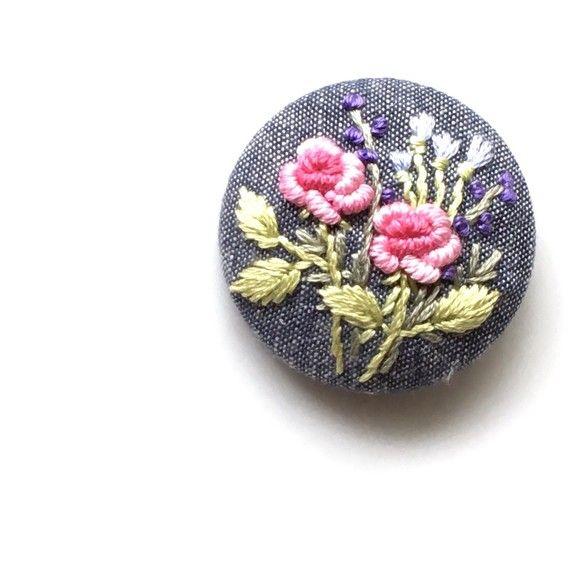 (こちらの作品は、他サイトでも販売中のため万が一注文が重なった場合は、同じ構図で新しく製作したものをお送りいたします。手刺繍ですので、全く同じにはならない場合もございますがあらかじめご了承ください。)バラの花をメインに、草花の刺繍をあしらった作品です。生地はネイビーのタンガリー。ヘアゴムに仕上げました。上品な刺繍の大きめくるみボタンで、存在感があります。ゴム部分は、好きな色 太さのものにかえてご利用いただいても良いように、あえて簡素な作りにしてあります。ヘアゴムの作品ですが、追加料金で、ブローチ仕様への変更が可能です。詳しくは商品名*ヘアゴムをブローチ仕様へ変更いたします*をご覧ください。手刺繍のため、同じものは二つとありませんが、同じモチーフでのオーダーは可能です。くるみボタン直径約4cmくるみボタン/金属生地、刺繍糸/綿