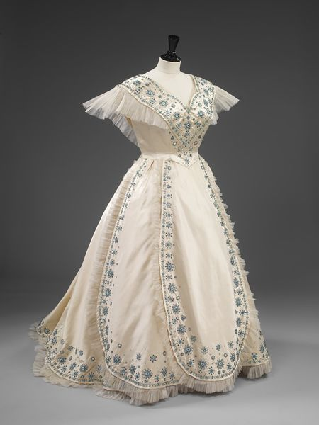 1953, State evening dress of white silk satin with aquamarine and turquoise beaded embroidery in a frosted flower design. With a fichu collar around low neckline, and decorative panels trimmed with pleated net on the full crinoline skirt. Designed by Norman Hartnell for Her Majesty Queen Elizabeth, the Queen Mother. Victoria & Albert Museum, London.