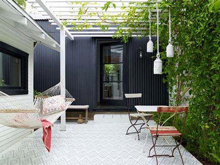 Een simpele tuin, maar door bepaalde elementen erg stijlvol en met heel veel sfeer. De interieurontwerper heeft gekozen voor een lichte kleine tegeltjes met een patroon. Deze geven de tuin een klein beetje een mediterrane gevoel. Dit gevoel wordt nóg meer benadrukt door de leuke lampionnen die boven de vintage stoelen en tafel hangen. De heerlijke hangmat maakt het natuurlijk helemaal af.