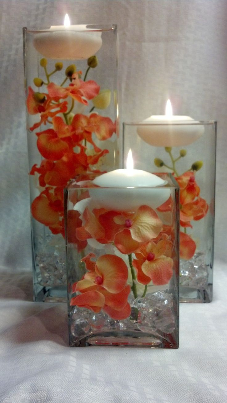 Three square vases with coral orchids and floating candles