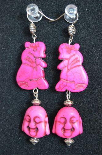 67 - 21    Mellanlånga örhängen, bestående av två pärlor i form av ett Buddha inspirerat ansikte och en sittande elefant, båda i rosa magnesit. Pärlorna kompletteras av små detaljer i silverpläterad metall och allergifria krokar.    Pris:  180 kr