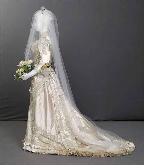 Wedding Gown, 1880    Wedding gown, 1880 & 1942  Silk satin, lace, glass beads, and net. No label. Worn by Annie Louisa Libby when she married William French Burrows, 1880 Worn again by granddaughter, Ruth Libby Burrows when she married Lawrence Dawson, 1942    This piece is part of the Chicago History Museum exhibition I Do! Chicago Ties the Knot. The exhibition explores an array of wedding traditions through costume, and how some of those traditions were standardized by Chicago retailers…