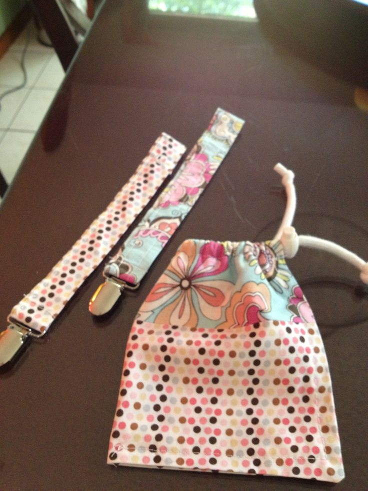 """I made """"binky"""" holders and a bag for the pacifier and holder to throw in the diaper for travel with the baby.  This cute fabric was left over from bibs I made earlier."""
