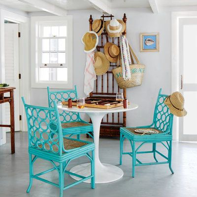 A chic game table and chairs earn a prominent spot just inside the front door. The hoop-back chairs (in Cooled Blue finish) are from Red Egg, and the hall rack is a French antique.
