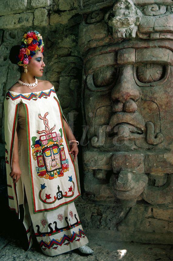 Young woman in Mayan dress posing by statue of Sun God at Mayan ruins of Kohunlich. Yucatan, Mexico.