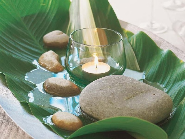 A tropical arrangement easy to make. Banana leaves, candles and spa looking rocks.