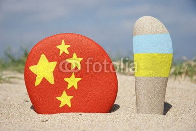China and Ukraine flags on stones with sand background