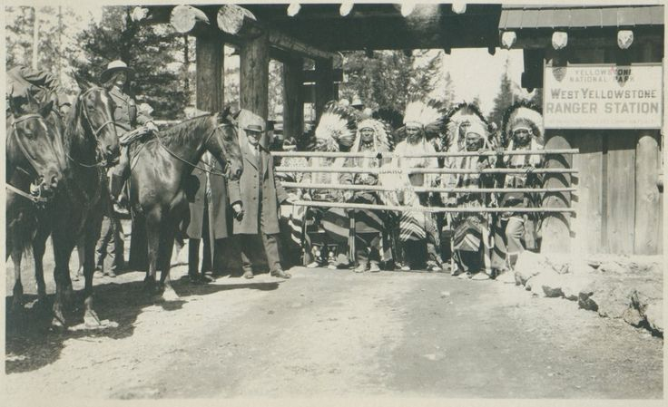 Indians performing at the West Yellowstone Ranger Station. Indians dressed in headresses and traditional clothing at the West Yellowstone Ranger Station next to the park rangers on horseback. (Вероятно Не Персе. Стоят слева предположительно Вождь Джозеф, Hustul ???) University of Wyoming. American Heritage Center.