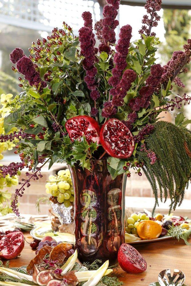 Para a mesa da Ceia de Natal, usamos tuias variadas, azevinhos, orquídeasdenphal, nas coresverde claro, hipérico, amaranthus e sementes de urtiga. Para arrematar a composição, usamos romã, pêssego e uva, que simbolizam fartura e alegria (para quem tem dúvidas sobre o uso de frutas em arranjos florais, vale a pena visitar opostArranjos com Flores e Frutas, ondefalamos sobre o assuntos).