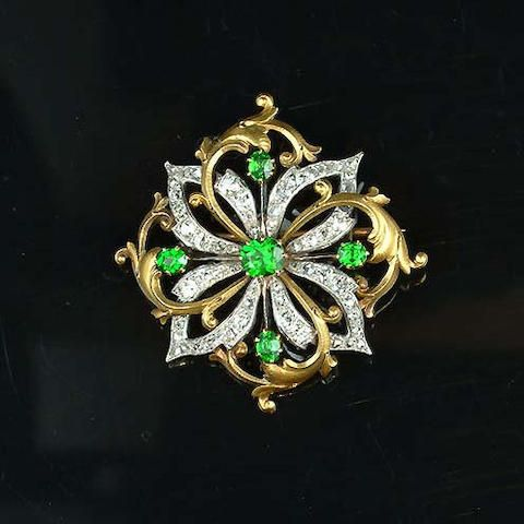 A demantoid garnet and diamond brooch, circa 1900, the lozenge-shaped plaque with old brilliant, single and rose-cut diamond flower-head entwined with gold foliate motifs and highlighted by five demantoid garnets, maker's mark and French assay marks to pin, width 3.6cm.