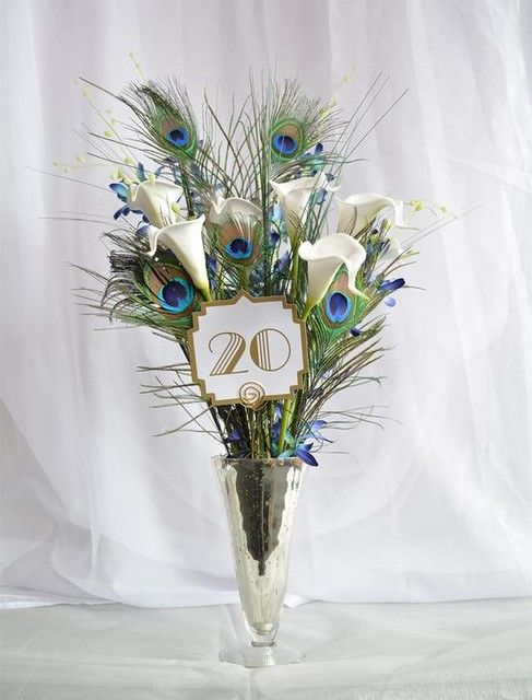 To make this beautiful Art Deco themed wedding centerpiece start by cutting a small piece of floral foam shaped to fit into vase and insert into vase.  Set 6 calla lilies into foam at slightly varying heights, next insert 3 mini orchid stems into vase aga