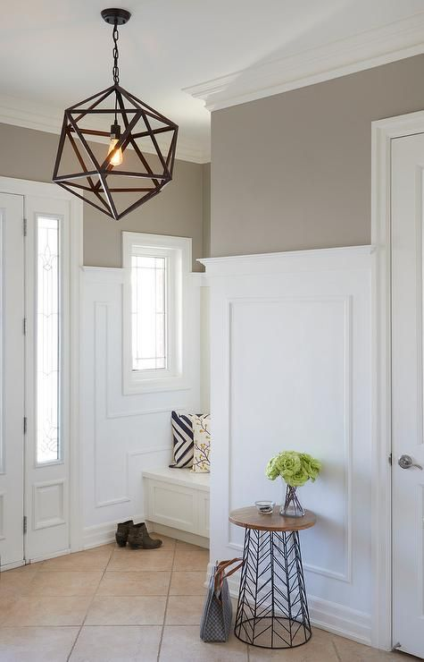 A white front door with sidelights opens to a white and taupe foyer boasting light taupe upper walls painted in Benjamin Moore Museum Piece and accented with tall white wainscoted lower walls.