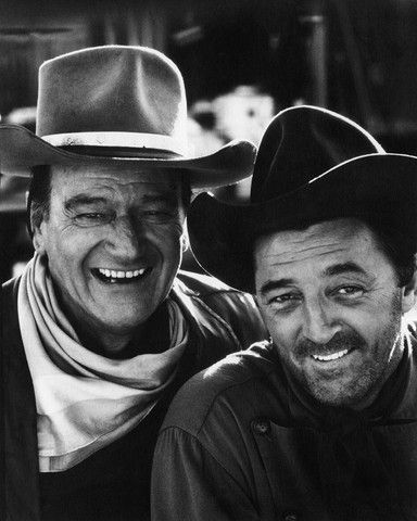 """John Wayne and Robert Mitchum, during the filming of """"El Dorado."""" Tucson, Arizona. [1967] Notes from John R. Hamilton: """"For the famous photos of Wayne-Mitchum, I said to John Wayne: 'Duke, I want to get a photograph of you two pro's together. This will be great!' When I first set up this shot, both were away from each other in the frame. I said, 'Come on, I want you really close. Come on, you two, get really close, as close as possible.' Robert Mitchum remarked, 'What do you want me to do…"""