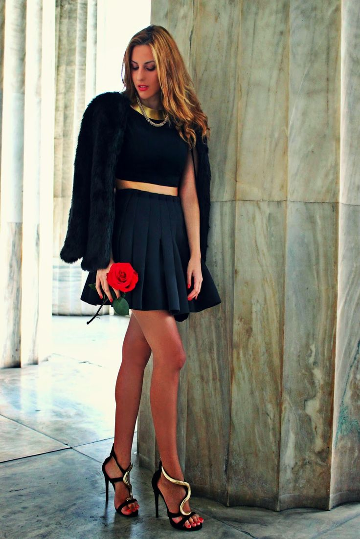 Shop this look on Lookastic:  http://lookastic.com/women/looks/cropped-top-heeled-sandals-necklace-fur-jacket-mini-skirt/4815  — Black Cropped Top  — Black and Gold Embellished Satin Heeled Sandals  — Gold Necklace  — Black Fur Jacket  — Black Pleated Mini Skirt