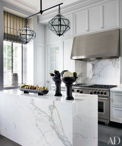 A marble island and backsplash in this kitchen | archdigest.com