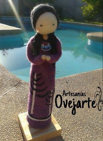 Escultura inspirada en la mujer mapuche con vestido decorado con araucarias y joyería