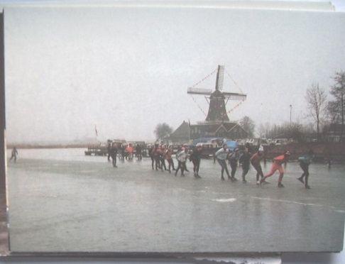 de 13e Elfstedentocht op 21 februari 1985 , zicht op toerrijders en de met vlaggetjes versierde houtzaagmolen De Rat in IJlst