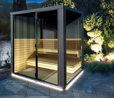 """Hochwertige Sauna im Garten: Der """"Atlas Cube"""" nachts und beleuchtet. Foto: Atlas Natursteine"""