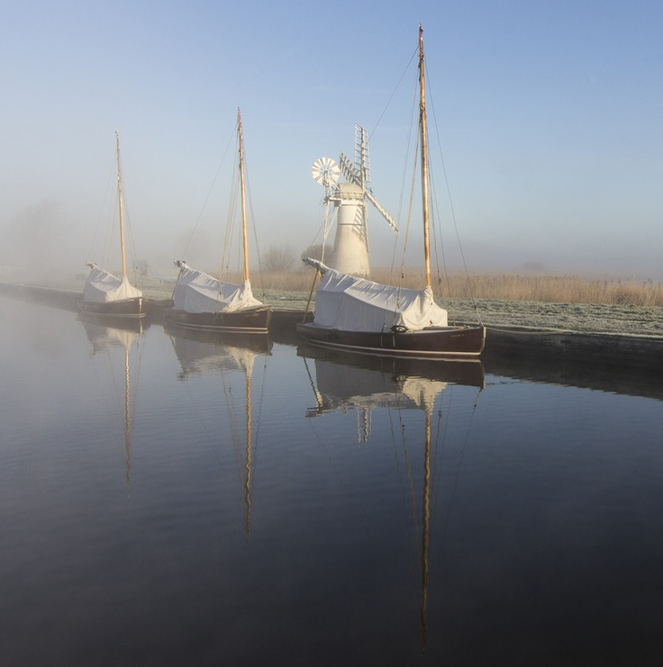 Three yachts at Thurne staithe on the river Bure. Thurne wind pump behind.