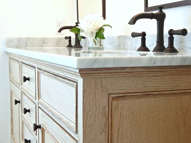 Light Oak with a minimal distressed finish makes up a dual washstand with a honed carerra marble countertop.