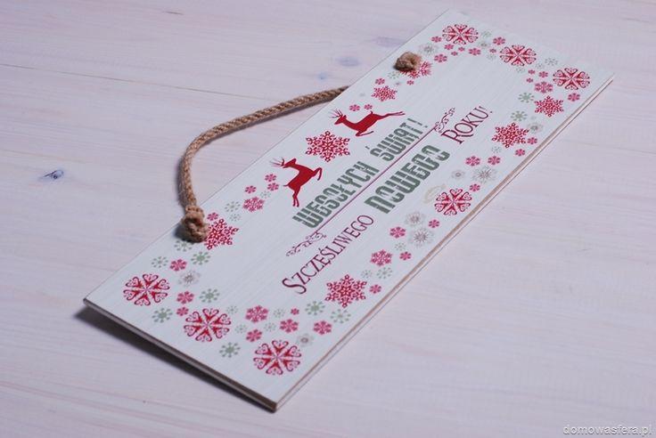 """Biała drewniana tabliczka z napisem: """"Wesołych Świąt! Szczęśliwego Nowego Roku"""". Zawieszona na drzwiach, dzięki jutowej lince, przywita gości Twojego domu. Urocza ozdoba, która stworzy świąteczny klimat."""