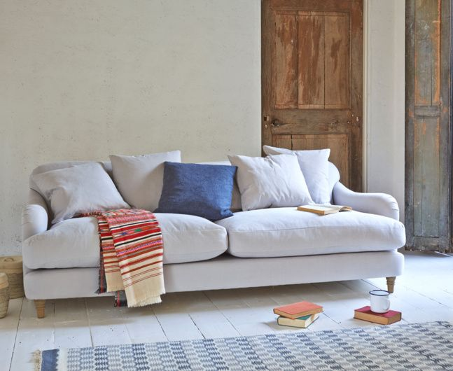 Our Achilles sofa is a deep sofa with scatter cushions for extra comfort that looks gorgeous. It is handmade in Blighty and comes in over 90 fabrics.