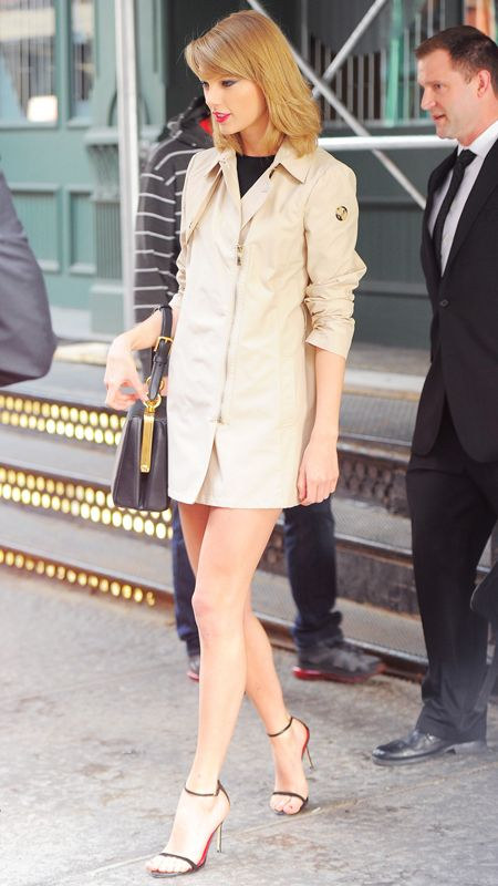 Taylor Swift in mini dress under a short trench, accessorized with simple black sandals and a black bag.