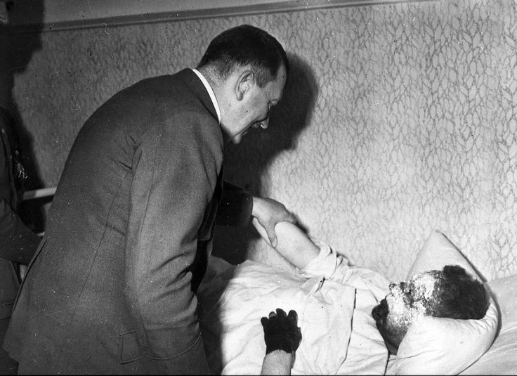 Hitler comforts a frostbitten German soldier who tries to salute him while in bed. Hitler gently sets his arm down to tell him to rest and recover. (1941)