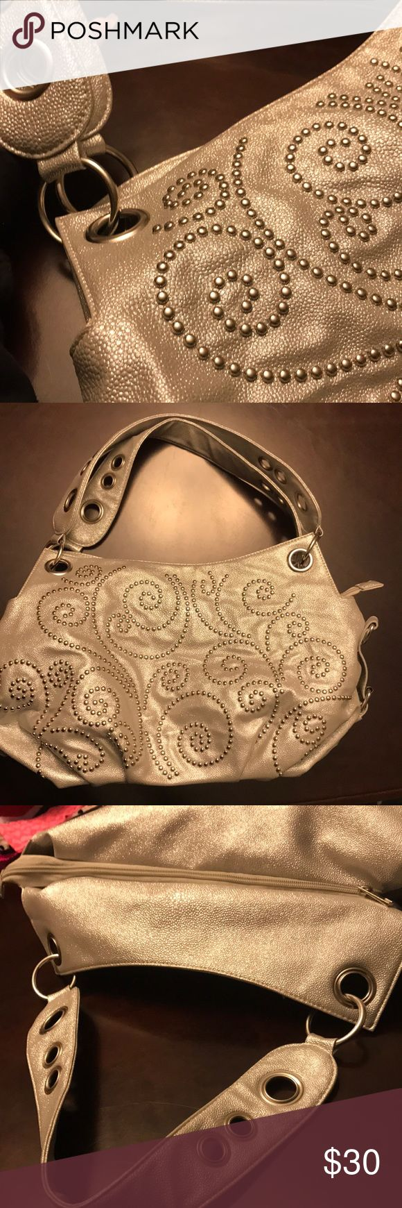 👛The Buckle metallic silver purse silver beading Youmi K The Buckle silver purse. Front of the purse has intricate silver beading over metallic silver. It has 2 shoulder straps which attach through 2 holes on each side. They are non-adjustable.  The back of the purse is a zippered pouch and a small pocket for a cell phone. The purse zippers closed & once opened there are 3 compartments/pockets. 1 side has a zippered pocket and the other has two smaller pockets. There are lots of pictures…