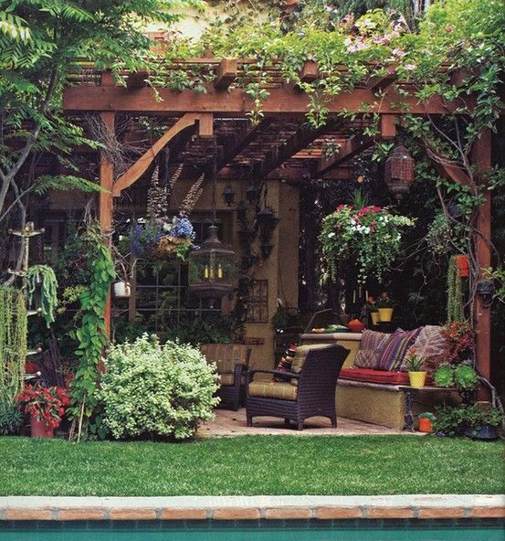 Overgrown pergola (with strings of lights!) over outdoor dining area/hangout