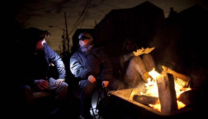 Residents stay warm by a fire in November 2012 in the Rockaway neighborhood of the Queens borough of New York City following power outages brought on by Superstorm Sandy. Photo: Allison Joyce/AFP