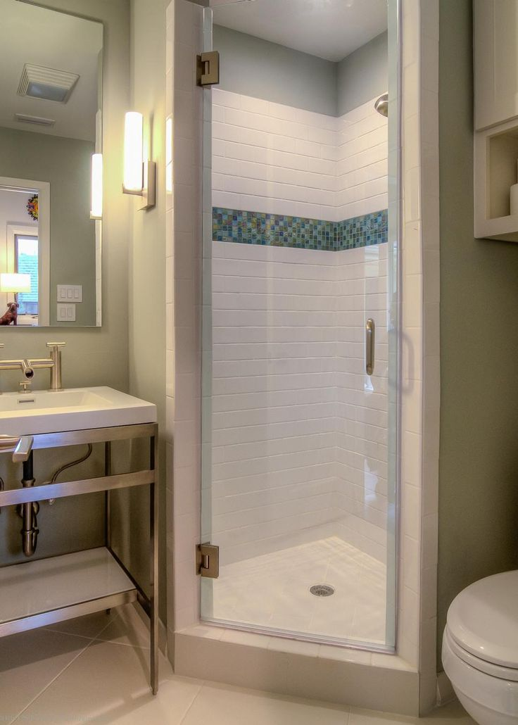 A stall shower fits perfectly in the corner of this small bathroom. Bright white tile and a sleek glass door help to make the small shower feel larger.