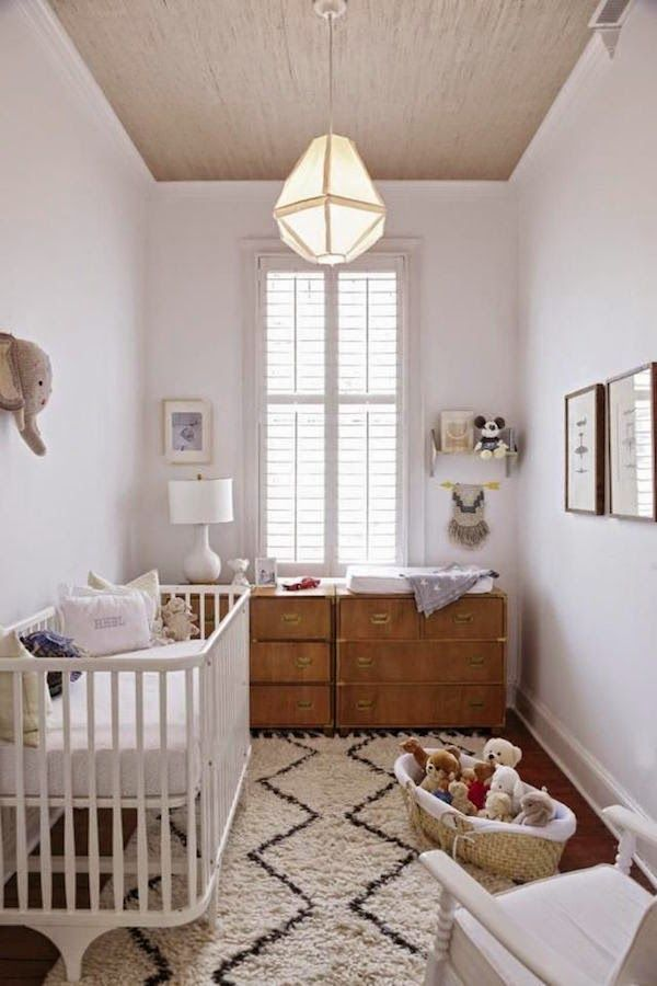 Mid-century modern inspired nursery. Very neutral and calming color scheme. Black and white rug, white crib, teak dresser, geometric light fixture