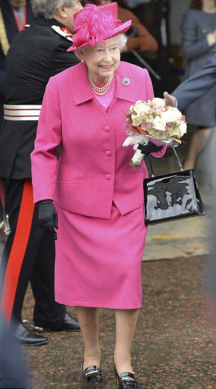 Her Royal Highness Queen Elizabeth II wore a colourful hot pink ensemble with a matching feathered hat as she greeted well-wishers outside the theatre, 22.10.13