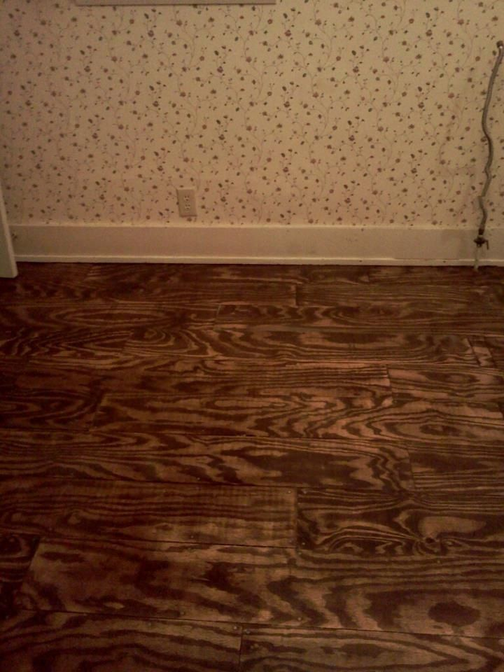 """This is a plywood floor. I chose sheets of plywood that was sanded on one side and full of knots. The Lowe's employee ripped the boards in half for me, the cut the halves into 6"""" planks.  I sanded them and stained each board twice, then my friend installed them with silver drywall nails. After they were installed he went over the floor with more stain then sanded the edges to make it look worn. Total cost for five boards, small can of stain and a box of nails- $68."""