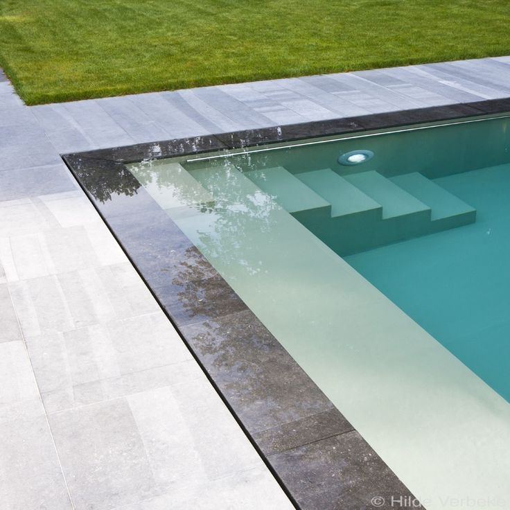 Sleek contemporary pool, combined underflow and overflow system | stone edging and immaculate lawn