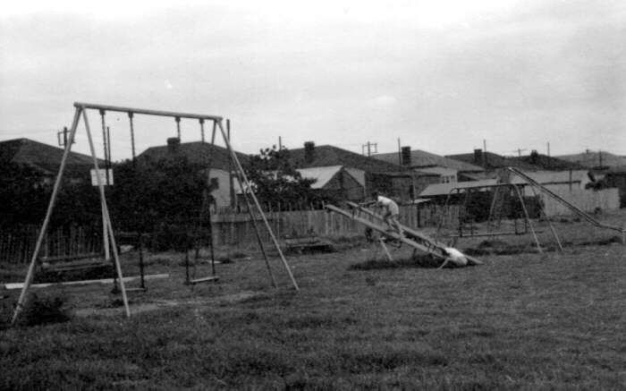 Old playground equipment - this one was in Newcastle 1953; we had the same kind if swings (with hard seats), seesaw, log swing and high metal slide at Greythorn Park, Vic.