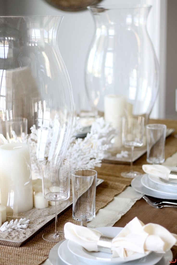 Hurricane glass, white candles & coral as table decoration