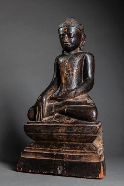 Buddha Maravijaya assis sur un socle étagé vêtu de la robe monastique, une main en bumishparshamudra et l'autre main en offrande dhyanamudra. Son visage serein aux yeux mi clos exprime la contemplation intérieure. Bois de teck laqué à traces de dorure. Birmanie. Royaume d'Ava. 16 ème siècle. Ht 49,5cm. Accidents, érosions et restaurations ancienne à la base