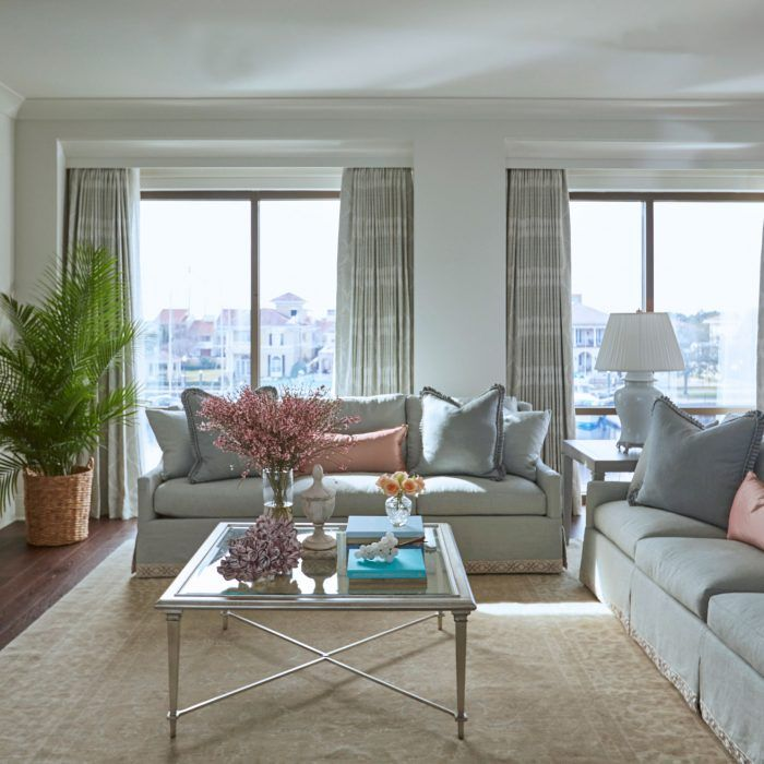 Pretty pastel living room featuring twin sofas, plush pillows, and a vintage rug.