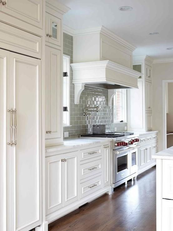 Love this kitchen- -White Kitchen 1 of 2 -Like hardwood floor color -white paneled hood with swing arm pot filler -wolf stove -cabinets installed over DOUBLE door refrigerator -subway tile backsplash