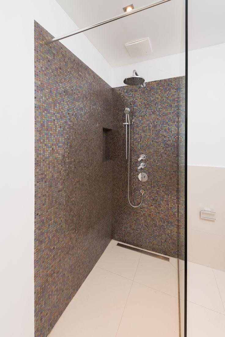 Dusche mit irisierendem Glasmosaik und großformatigen Fliesen. Foto: Daniel Schvarcz Photographie