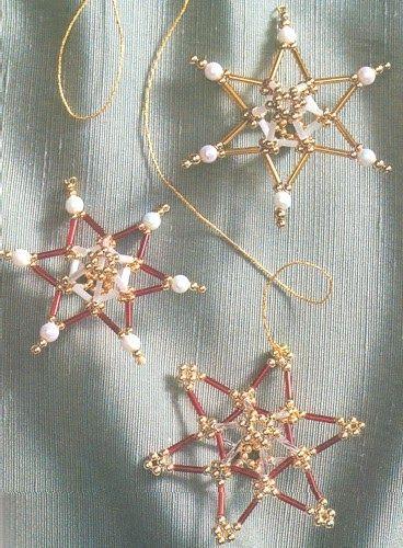 ESTRELLAS CON CORAZON 3D Materiales: Estrella color rojo/oro Cuentas doradas de 3 mm Canutillos rojos y plateados de 9 mm Estrella de color...