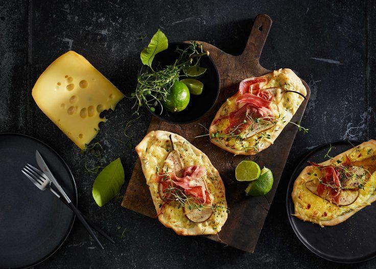 Oppskrift på fire minipizzaer med tynn bunn toppet med Jarlsberg®,   crème fraîche, serranoskinke, pære og timian.