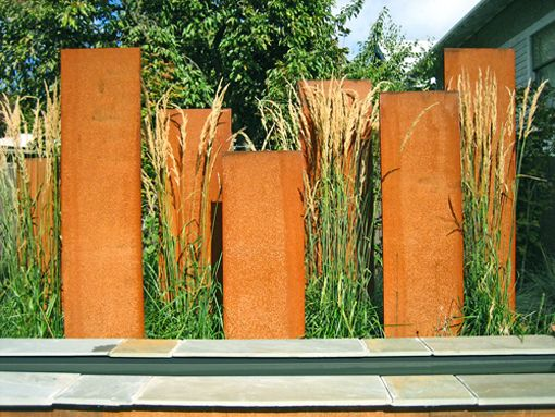 clôture mixte : panneaux de métal rouillé + myscanthus