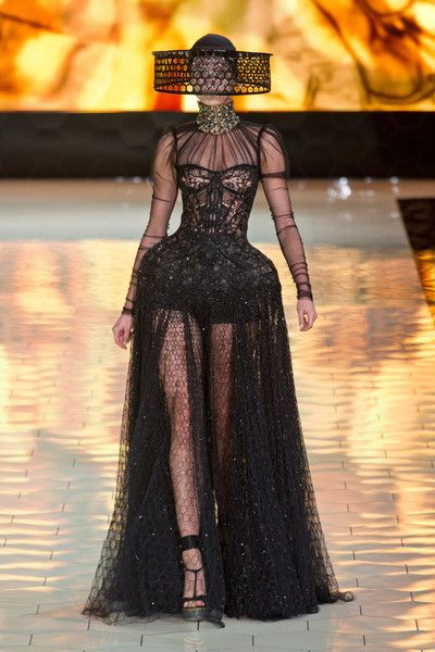 Alexander McQueen Spring 2013. We see the head ornament. The top of the dress looks like a chemise. The necklace is gorgière inspired. The skirt is big to show a slim waistline and the garment has a lot of lace and embroideries.