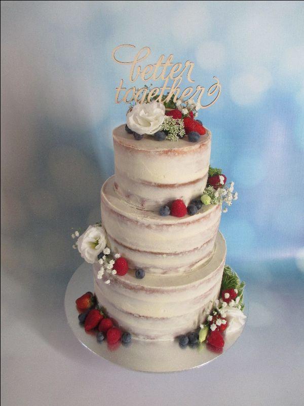 Semi-naked wedding cake with berries & fresh flowers